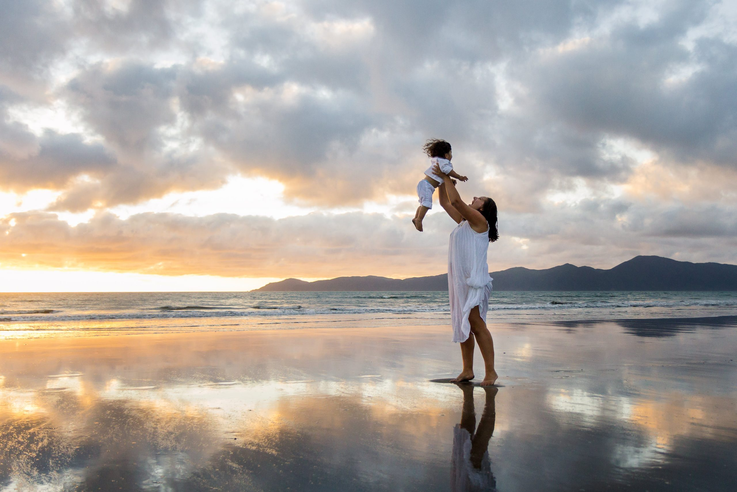 Mum standing on a Paraparaumu beach in front of Kapiti Island at sunset and holding up her little boy with reflections in the sand