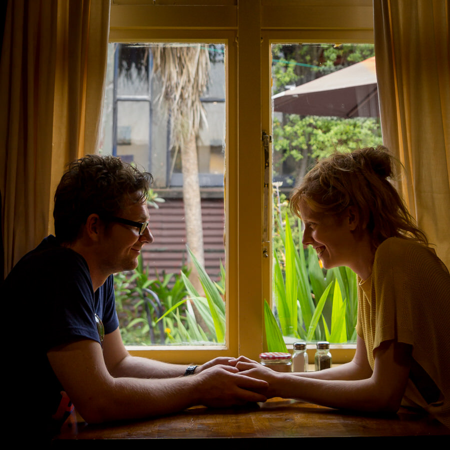 Lianna and her husband looking at each other in front of a mustard coloured window in a cafe