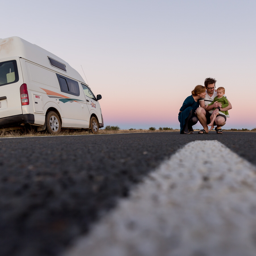 Family of three standing on an empty road next to a Hippie Campervan