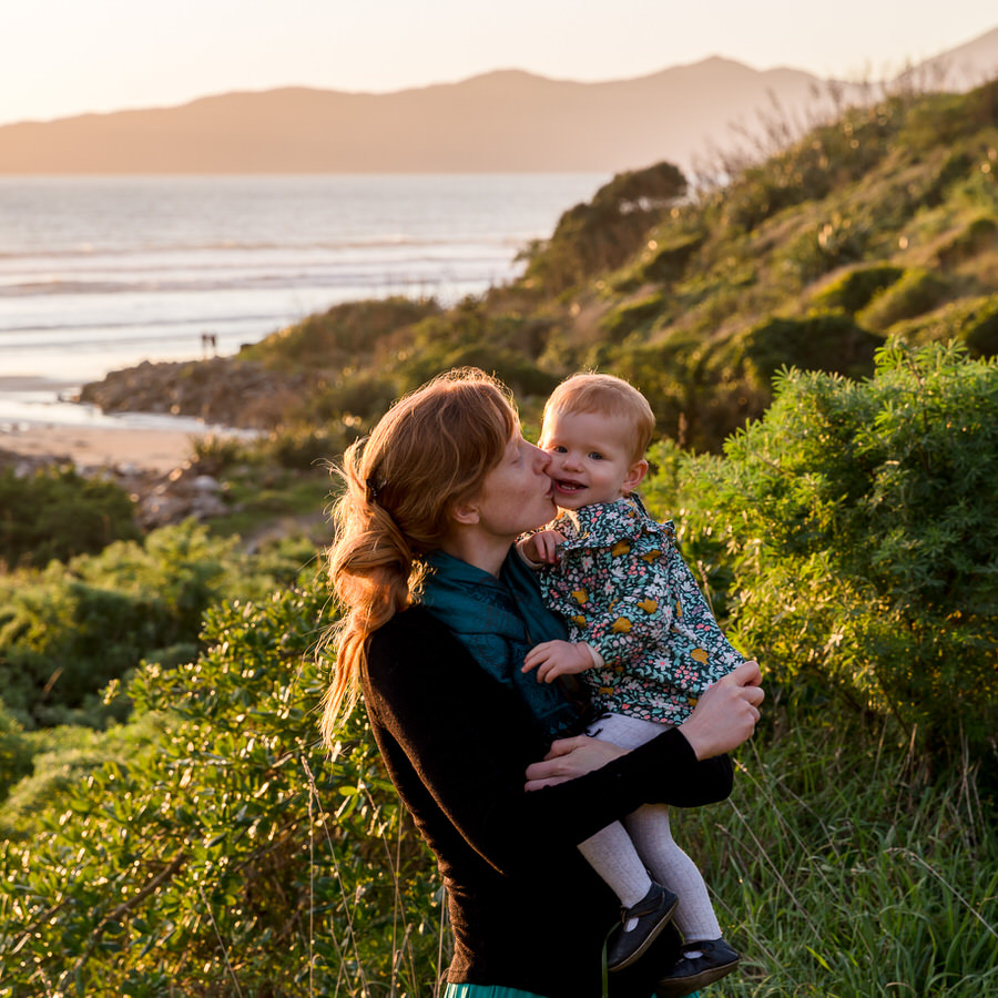 Mum kissing a toddler standing in the hills in Queen Elizabeth Park at sunset with Kapiti Island in the background
