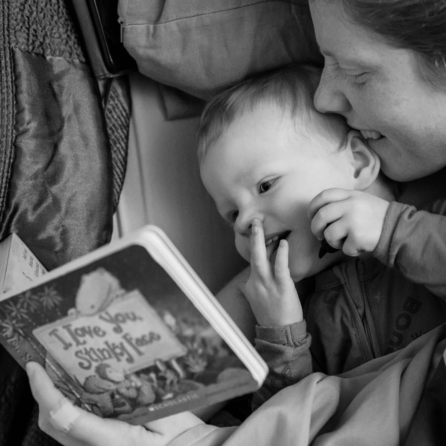 Black and white photo of Lianna biting her daughter's ear while reading a book in bed called I love you stinky face
