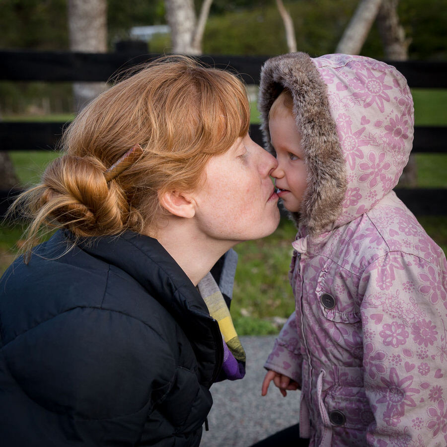 Mum kissing a toddler who is wearing a purple floral jacket with a hood