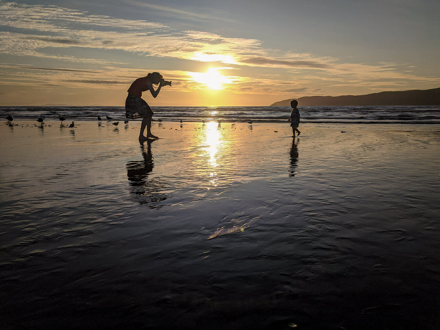 Silhouette of Lianna photographing a child on Paraparaumu Beach in front of Kapiti Island