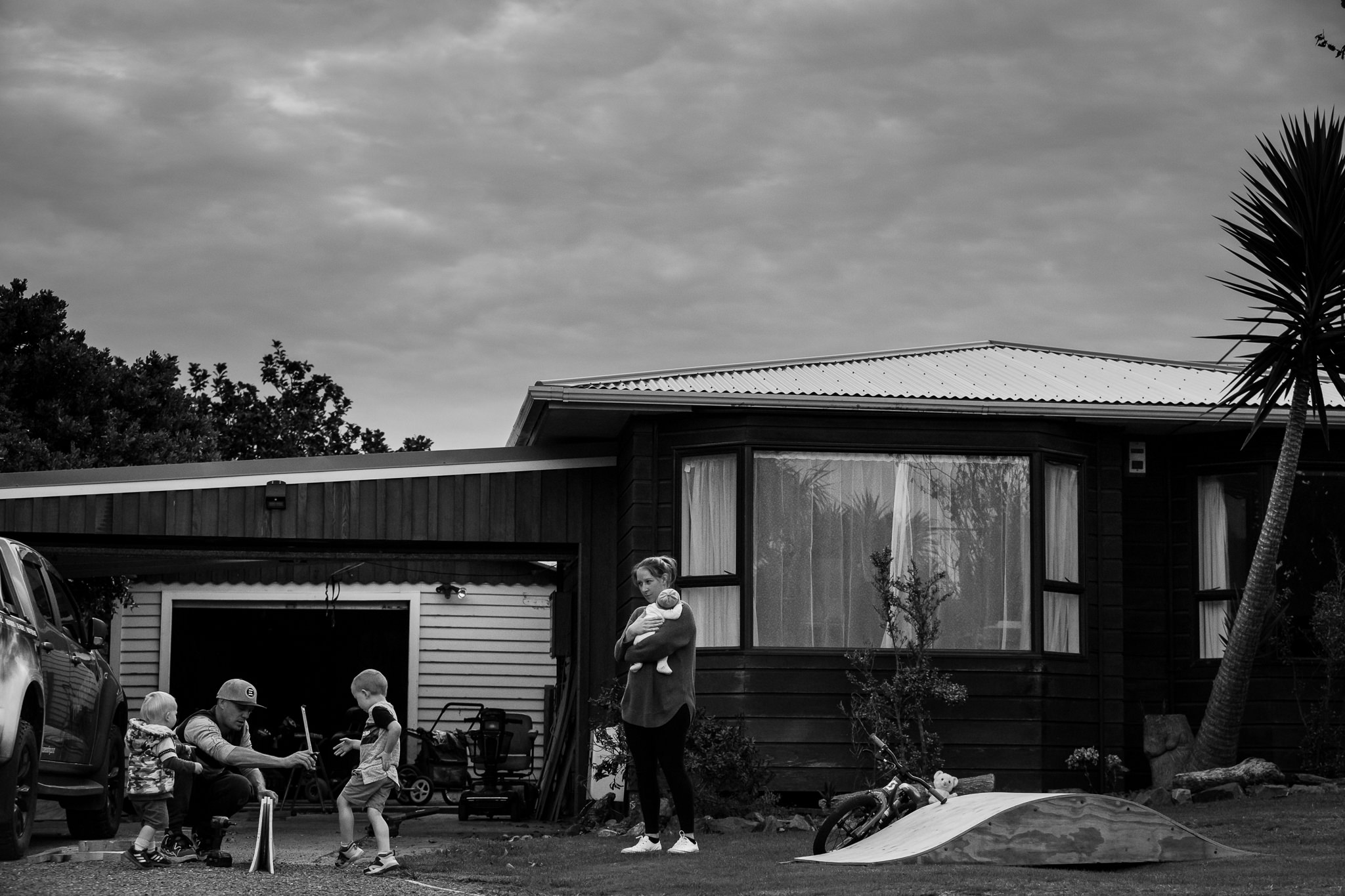 Photograph of a family standing outside their home in Raumati