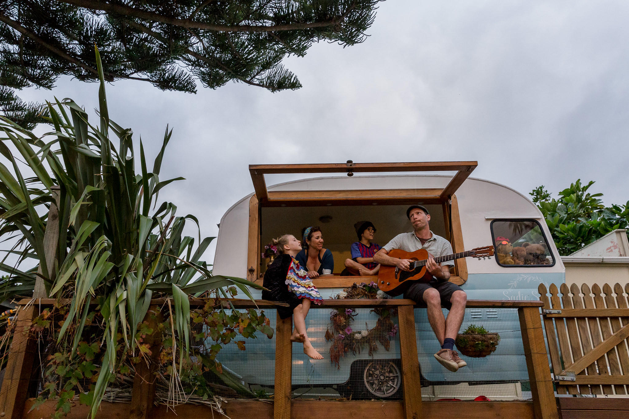 Photo of a family sitting in their caravan outside their home in Raumati