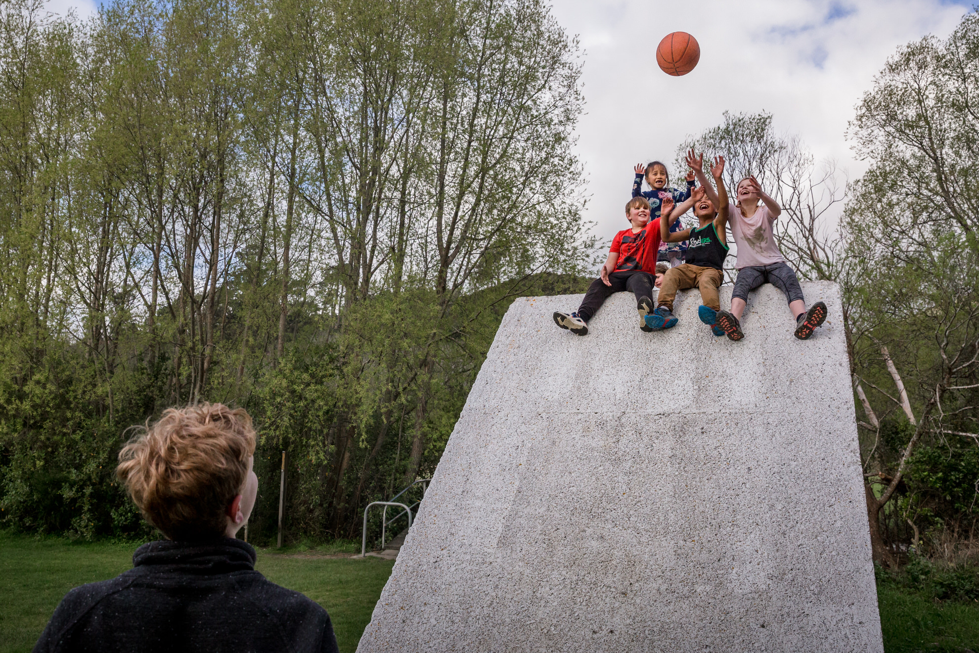 Boy throwing a ball to a group of children sitting on top of a wall